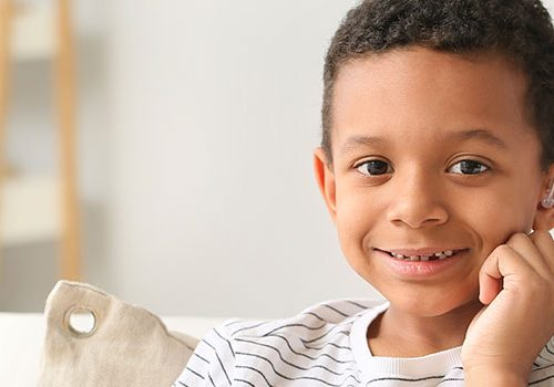 Young boy wearing a hearing aid.